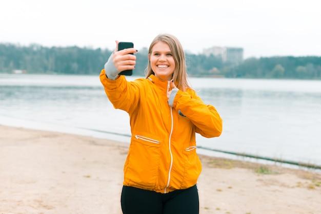 흥분된 웃는 소녀는 공원 호수 근처에서 야외에서 셀카 또는 화상 채팅을하고 있습니다.