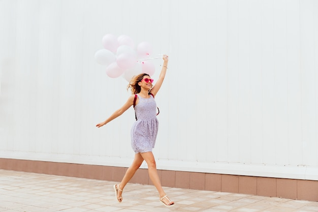 Excited smiling girl in pink sunglasses running with balloons, wearing dress and sandals
