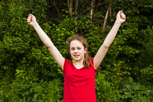 Excited smiling girl raised hands in success gesture at park