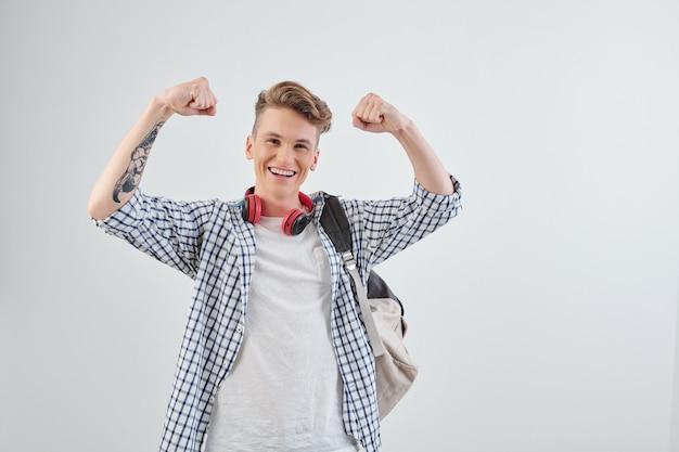Возбужденный улыбающийся старшеклассник поднимает руки и демонстрирует мускулы, гордясь своими достижениями