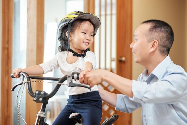 자전거를 타는 방법을 설명하는 그녀의 아버지를보고 흥분 웃는 어린 소녀