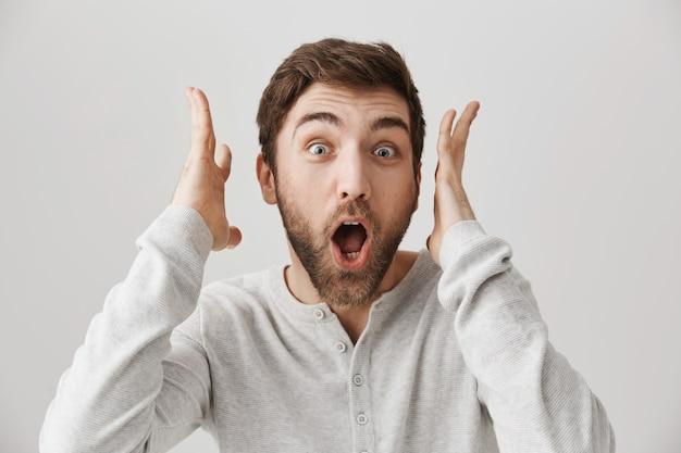 Взволнованный улыбающийся мужчина реагирует на потрясающие новости