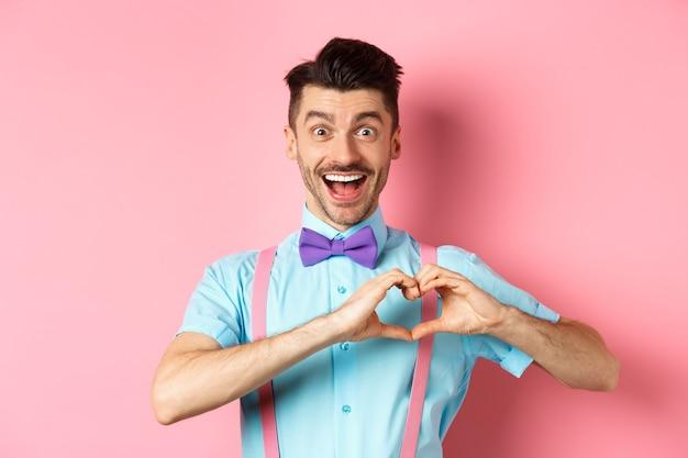 ロマンチックなピンクの背景の上に立って、ドキドキする心を示し、愛を込めて見ている興奮した笑顔の男。バレンタインデーのコンセプト。