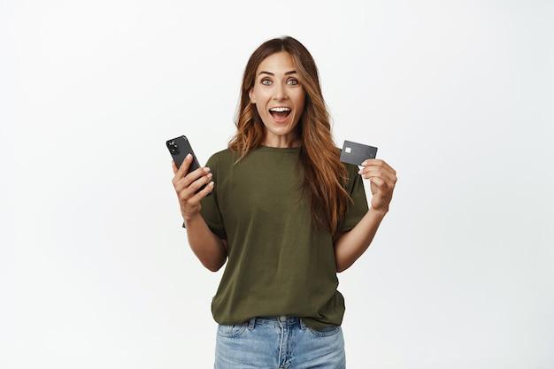 Eccitato sorridente donna di mezza età, tenendo lo smartphone, mostrando carta sconto di credito
