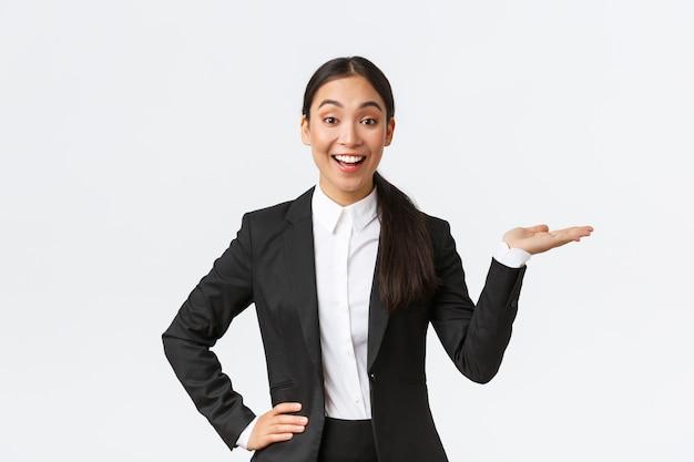 Взволнованная улыбающаяся продавщица представляет товар, пытаясь продать что-то на белом copyspace. довольно азиатская женщина-менеджер показывает проект, указывая рукой вправо и выглядит оптимистично, белый фон
