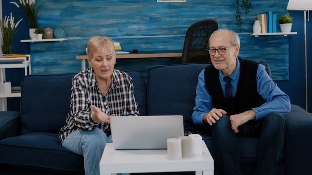 Excited smiling senior couple looking at laptop computer waving during videocall sitting at couch. cheerful retired husband and wife laughing talking at virtual meeting resting on sofa in cozy room.