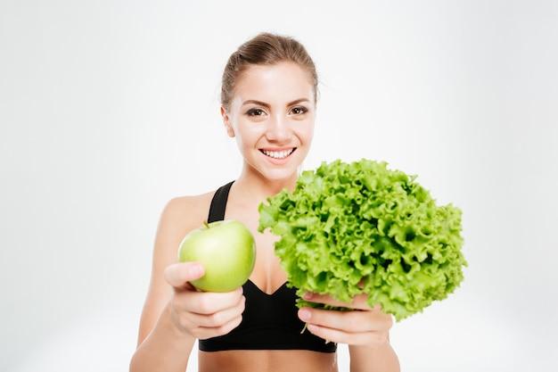 孤立したレタスと青リンゴを示す興奮した笑顔のスポーツ女性