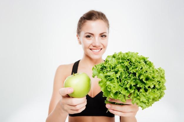 Взволнованная улыбающаяся спортивная женщина, показывающая салат и зеленое яблоко, изолированные