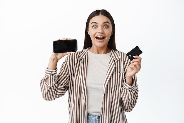 Eccitata donna sorridente guadagna soldi online, mostrando la carta di credito in plastica e lo schermo vuoto dello smartphone orizzontalmente, in piedi in abito elegante contro il muro bianco
