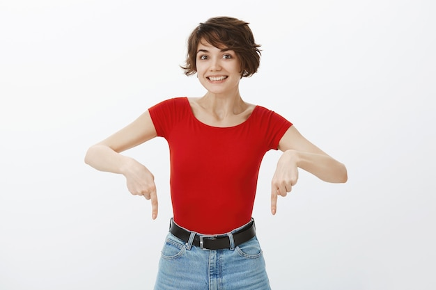흥분된 웃는 여자가 좋은 제품을 발견하고 손가락을 아래로 가리키며 멋진 프로모션 제안을 보여줍니다.