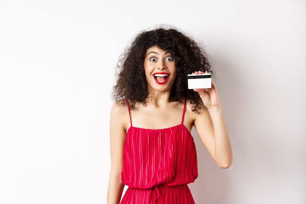 赤いドレスを着て、プラスチックのクレジットカードを表示し、白い背景の上に立って幸せそうに見える興奮した笑顔の女性。コピースペース
