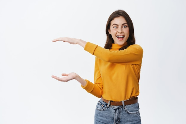 Excited smiling woman showing big object with hands on empty space, shaping box, sanding against white wall