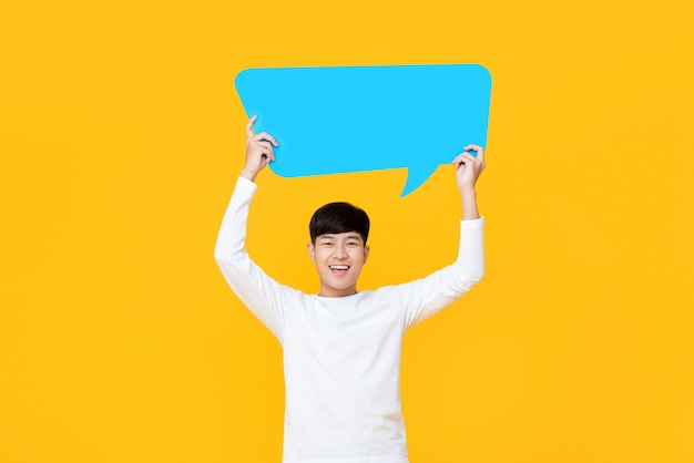 Excited smiling young cute asian man holding blue speech bubble