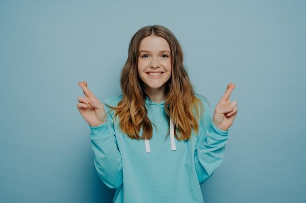 水色のスタジオの背景に分離されたカジュアルなセーターのポーズを着てカメラを見て指を交差させたまま波状のオンブルの髪を持つ興奮した笑顔の若い女の子。ボディーランゲージの概念