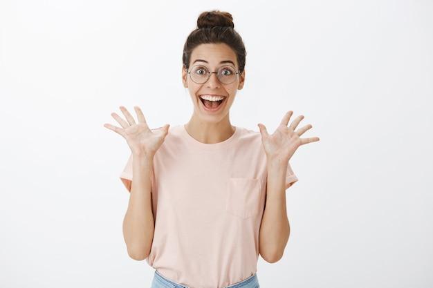 Возбужденная улыбающаяся молодая стильная женщина позирует у белой стены