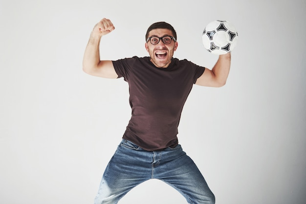 Excited поклонник футбола при футбол изолированный на белизне.