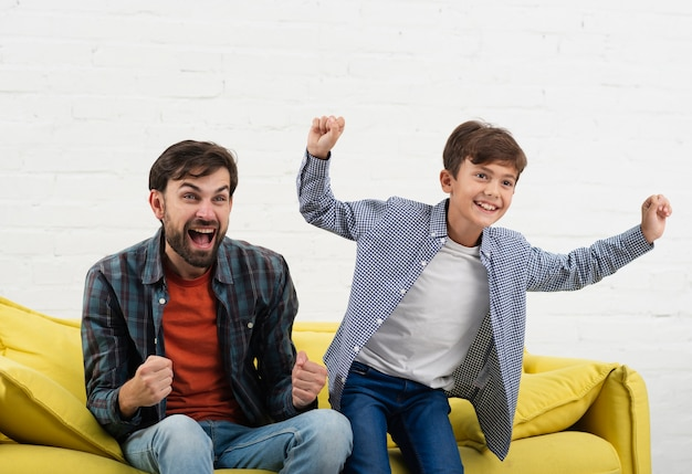 Excited son and father sitting on sofa