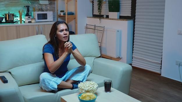흥분된 스포츠 팬은 소파에 앉아 tv로 온라인 게임을 보고 있습니다. 좋아하는 축구 팀을 지원하고 경쟁에서 비명을 지르는 잠옷을 입은 집에 혼자 있는 여자. 텔레비전 앞에서 저녁을 즐기고 있다.