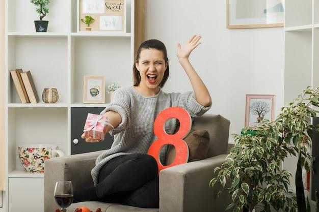 Eccitata mano allargata bella ragazza durante la felice giornata delle donne che tiene il presente alla telecamera seduta sulla poltrona in soggiorno