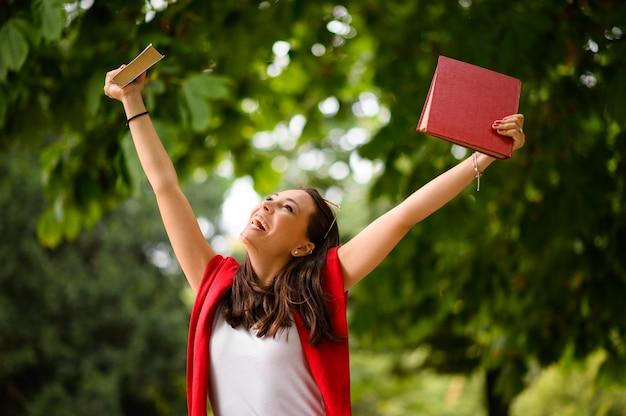 屋外で祝う拳を上げる興奮した学生の女の子
