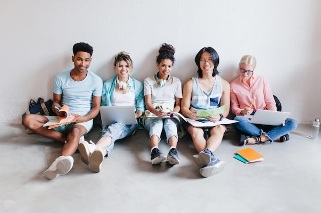 床に座ってテストの準備をしているラップトップと教科書で興奮している学生。試験前に一緒に勉強している国際的な友人の屋内の肖像画。