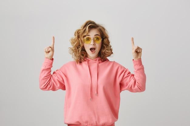 Eccitata ragazza riccia elegante che punta le dita verso l'alto per mostrare la pubblicità
