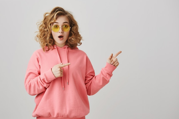Excited stylish curly-haired girl in sunglasses pointing right, showing way