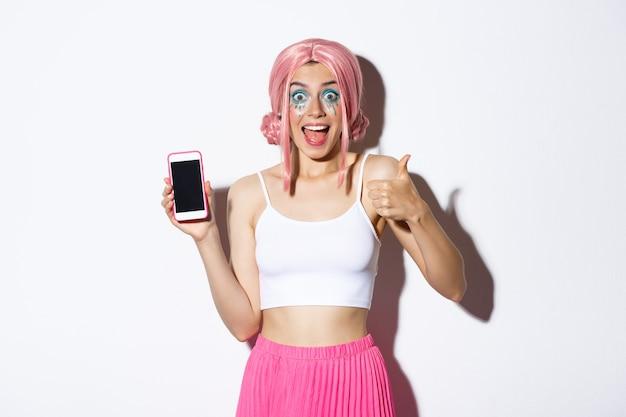 ピンクのかつらで興奮したスタイリッシュな女の子は、白い背景の上に立って、携帯電話の画面で素晴らしいものを見せながら、親指を立てて魅了されているように見えます。
