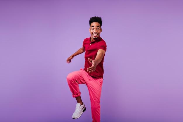 어두운 피부 춤으로 흥분된 세련된 남자. 갈색 머리 아프리카 남자 점프 웃음의 실내 사진입니다.
