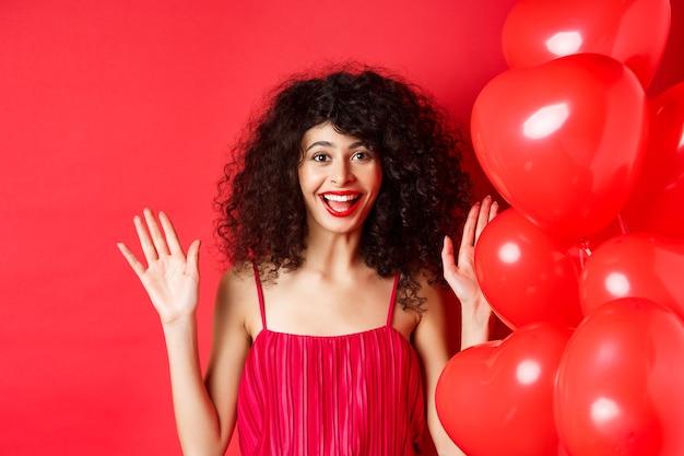 곱슬 머리를 가진 흥분된 세련된 여자, 드레스를 입고, 손을 올리고 행복하게 웃고, 심장 풍선, 흰색 배경 근처에 서.