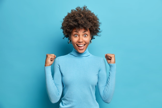 Eccitata donna afroamericana di successo stringe i pugni celebra il successo nella carriera dice sì sorride ampiamente