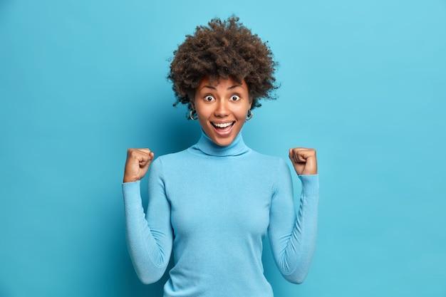 흥분된 성공적인 아프리카 계 미국인 여성이 주먹을 움켜 쥐고 경력 성공을 축하합니다