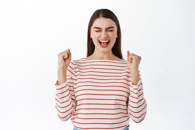 達成を祝い、勝利と叫び、拳ポンプを作り、彼女の目標を達成し、勝利を勝ち取り、白い壁の上に立って、興奮した成功した女の子
