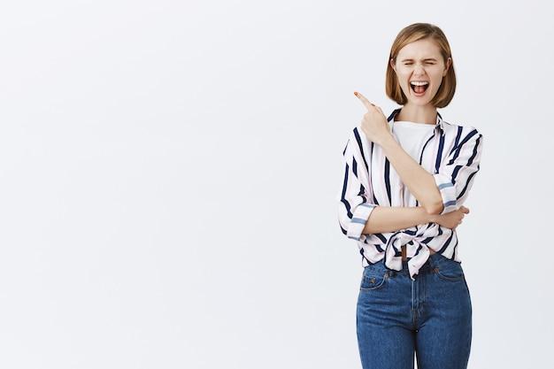 Возбужденная, очень счастливая молодая женщина указывает верхний левый угол на copyspace