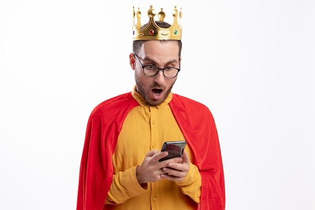 Uomo eccitato del supereroe in vetri ottici con corona e mantello rosso tiene e guarda il telefono isolato sul muro bianco