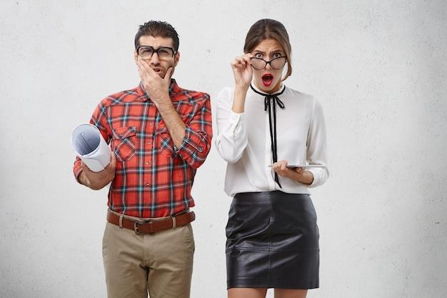 La donna adorabile sorpresa eccitata guarda attraverso gli occhiali, tiene il moderno tablet pc aiuta il maschio a creare schizzi