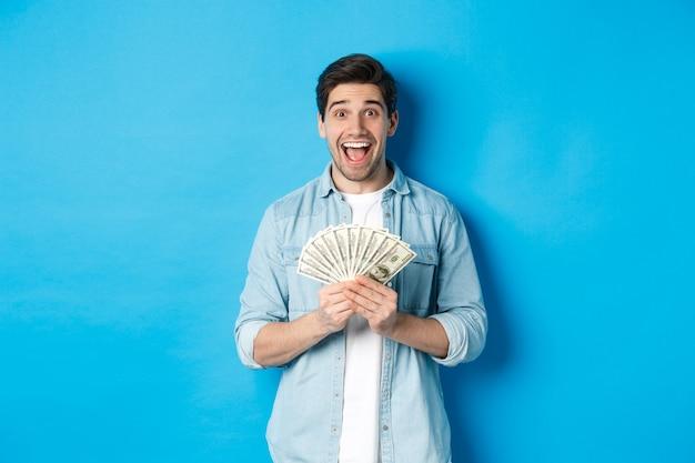 Eccitato e sorpreso uomo attraente, in possesso di un premio in denaro e sorridente stupito, in piedi su sfondo blu