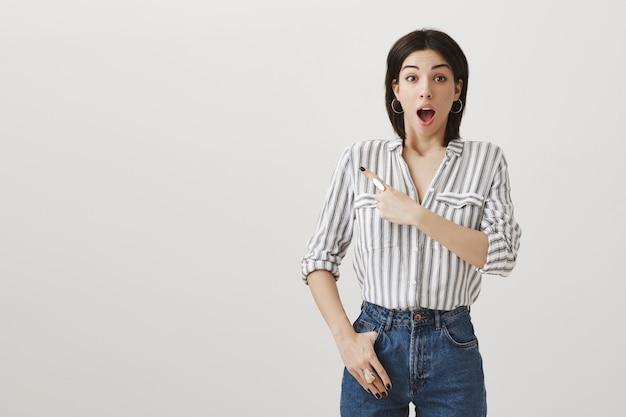 Взволнованная удивленная привлекательная женщина, указывающая пальцем в верхнем левом углу на потрясающее объявление