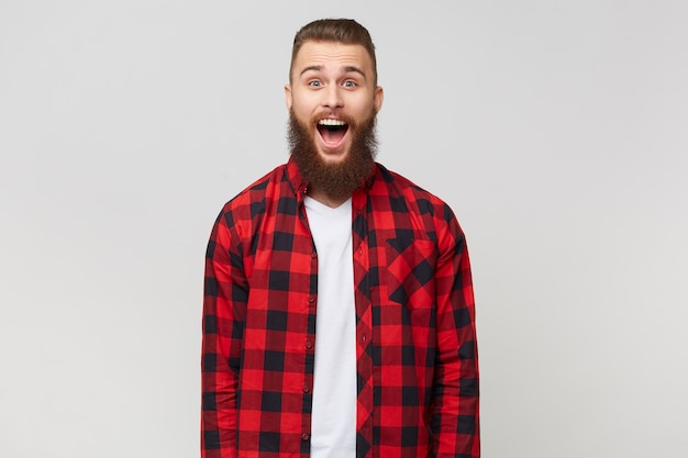 Excited surprised attractive young bearded guy in checkered shirt, opened mouth because of amazement, with mustache fasion hairstyle, isolated on white background