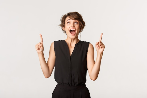 Excited and surprised attractive young woman looking and pointing fingers up at banner.