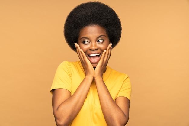 흥분된 흑인 소녀는 흥분과 긍정적인 충격으로 비명을 지르며 입을 벌리고 옆으로 쳐다본다