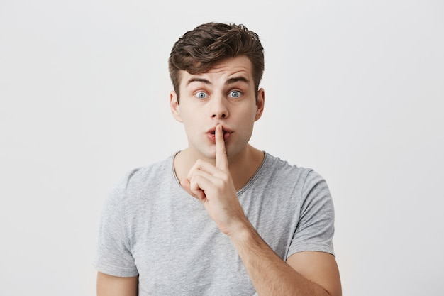 Excited surprised caucasian guy with stylish hairstyle casually dressed showing silence sign asking to be quiet. indoor portrait of handsome attractive male with bugged eyes holding finger on lips