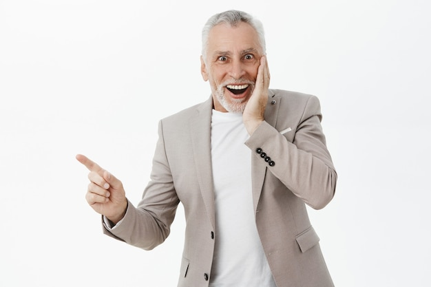 Excited and surprised elderly man pointing finger left and smiling amazed
