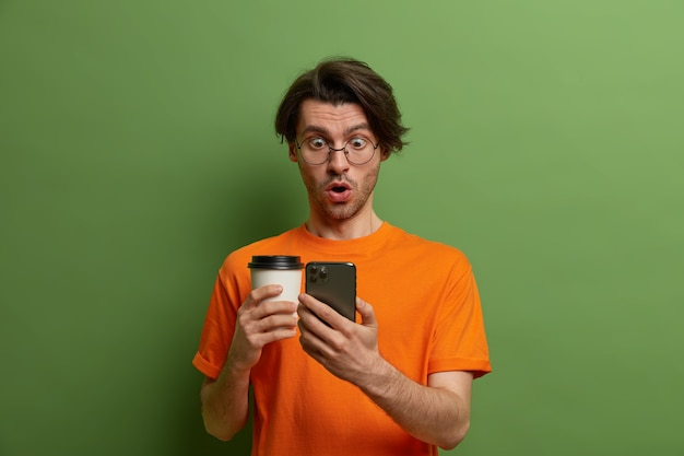 Uomo europeo sorpreso eccitato che fa schioccare gli occhi allo smartphone, sussulta per lo stupore, legge notizie incredibili in uno smart phone, beve caffè da asporto, è intenso e stordito, isolato su verde