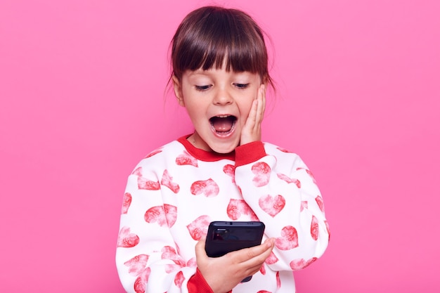 Excited surprised female child in casual style sweater holding smart phone in hands and keeping mouth opened, touching her cheek with palm, look at phone, posing isolated over pink wall.