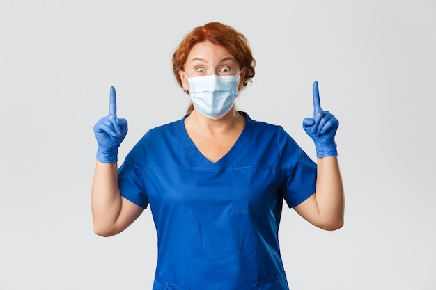 Excited and surprised female doctor, nurse in face mask, rubber gloves and scurbs look thrilled at camera, showing top banner, pointing up.