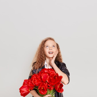 Excited surprised little girl with blonde wavy hair embracing bouquet of red tulips and looking up with opened mouth, keeping hand on her cheek