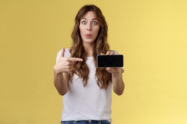 흥분된 놀란 소녀 곱슬거리는 긴 헤어스타일 접는 입술 휘파람을 부는 재미있는 응시 카메라는 스마트폰을 가리키는 검지 손가락 모바일 휴대폰 화면 스탠드 노란색 배경을 보여주는 감동을 받았습니다.