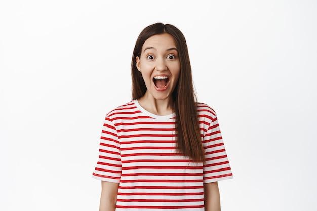 흥분한 놀란 여성이 턱을 떨어뜨리고, 놀라서 비명을 지르며, 놀란 앞을 바라보고, 흰 벽에 줄무늬 티셔츠를 입고 서 있는 그녀를 놀라움으로 쳐다보고 있습니다.