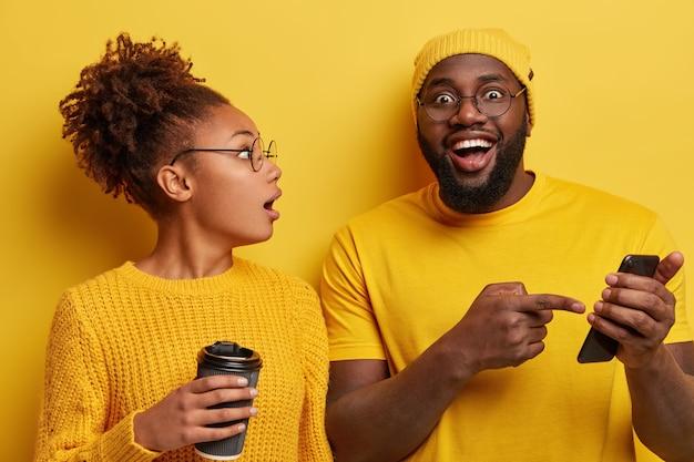La donna sorpresa eccitata ascolta con il modello maschio di grande interesse che racconta grandi opportunità e funzioni del nuovo smartphone